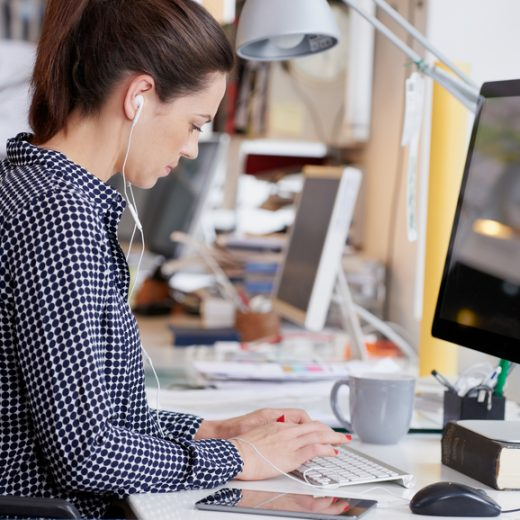 Start up businesswoman working at computer in busy office using technology